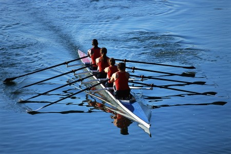 four rowers rowing a boat on open water